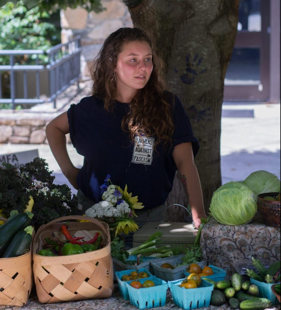 Clare Cameron, a senior at Warren Wilson College, at her work assignment managing a farmer's market. Photo: Jesse Pratt Lopez for The Hechinger Report