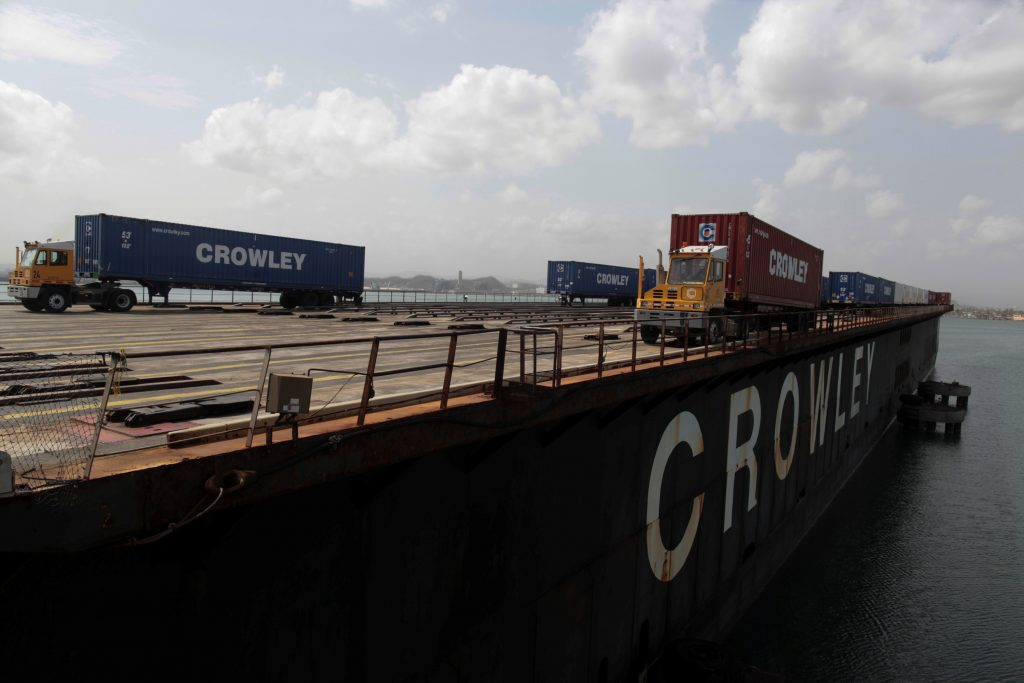 Workers unload containers of shipping company Crowley from a barge after the area was hit by Hurricane Maria at the port in San Juan, Puerto Rico, September 26, 2017. REUTERS/Alvin Baez - RC1852F03210