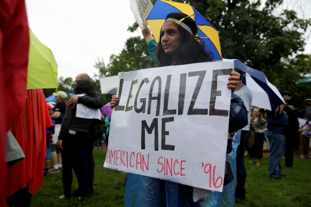 A woman holds a sign calling for her legalization during a rally by immigration activists CASA and United We Dream demanding the Trump administration protect the Deferred Action for Childhood Arrivals (DACA) program and the Temporary Protection Status (TPS) programs, in Washington, U.S., August 15, 2017. REUTERS/Joshua Roberts - RC1D815EA100
