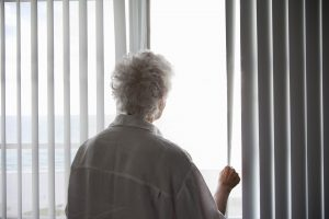 Senior Woman looking out of a window