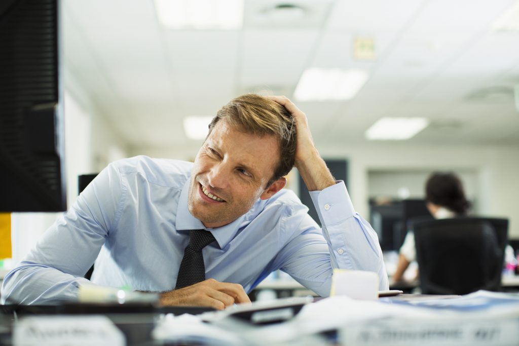 Businessman squinting at desk in office