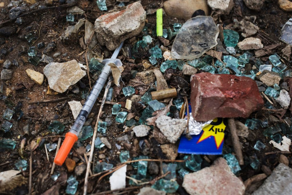 Broken glass and a discarded needle are seen near a heroin encampment in the Kensington neighborhood of Philadelphia, Pennsylvania, on April 7, 2017.