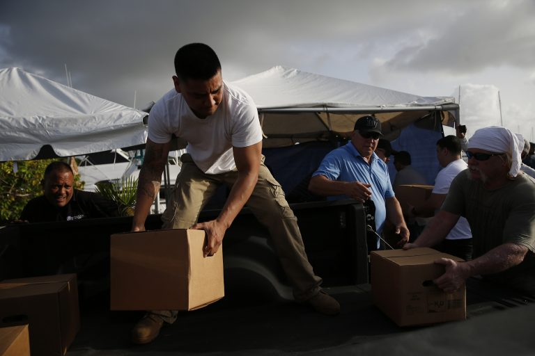 FAJARDO, PUERTO RICO - SEPTEMBER 12: Volunteers unload a pick up truck full of supplies headed for St. Thomas and St. John in Fajardo, Puerto Rico on Sep. 12, 2017. Volunteers were on the docks repackaging a variety of relief supplies into plastic boxes that can more easily make the journey across the Caribbean Sea to the islands, where Hurricane Irma slammed the region as a Category 5 storm last week. (Photo by Jessica Rinaldi/The Boston Globe via Getty Images)