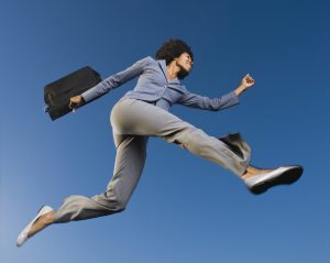 Businesswoman carrying briefcase in mid-air Photo by Getty images