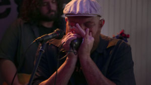 """Marcus Oglesby plays harmonica with his band, Creek Don't Rise, and sings """"White Coat Man,"""" a song he wrote in response to the mark opioids left on his hometown in West Virginia. Photo by Abbey Oldham"""