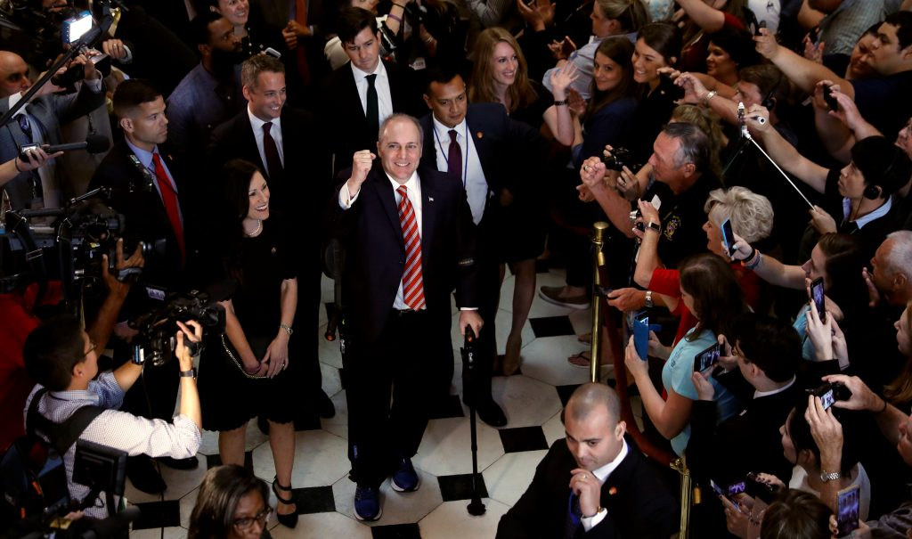 U.S. Rep Steve Scalise (R-LA), with his wife Jennifer at his side, pumps his fist as he makes his way through the U.S. Capitol after returning to Congress for the first time since being shot and seriously wounded in June, in Washington, U.S., September 28, 2017. REUTERS/Kevin Lamarque - RC1367EF95C0
