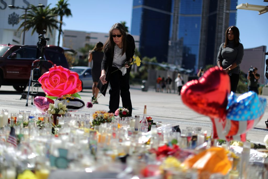 A woman leaves flowers on Oct. 3 at a makeshift memorial on the Las Vegas Strip for victims of the Route 91 music festival mass shooting. Photo by Lucy Nicholson/Reuters