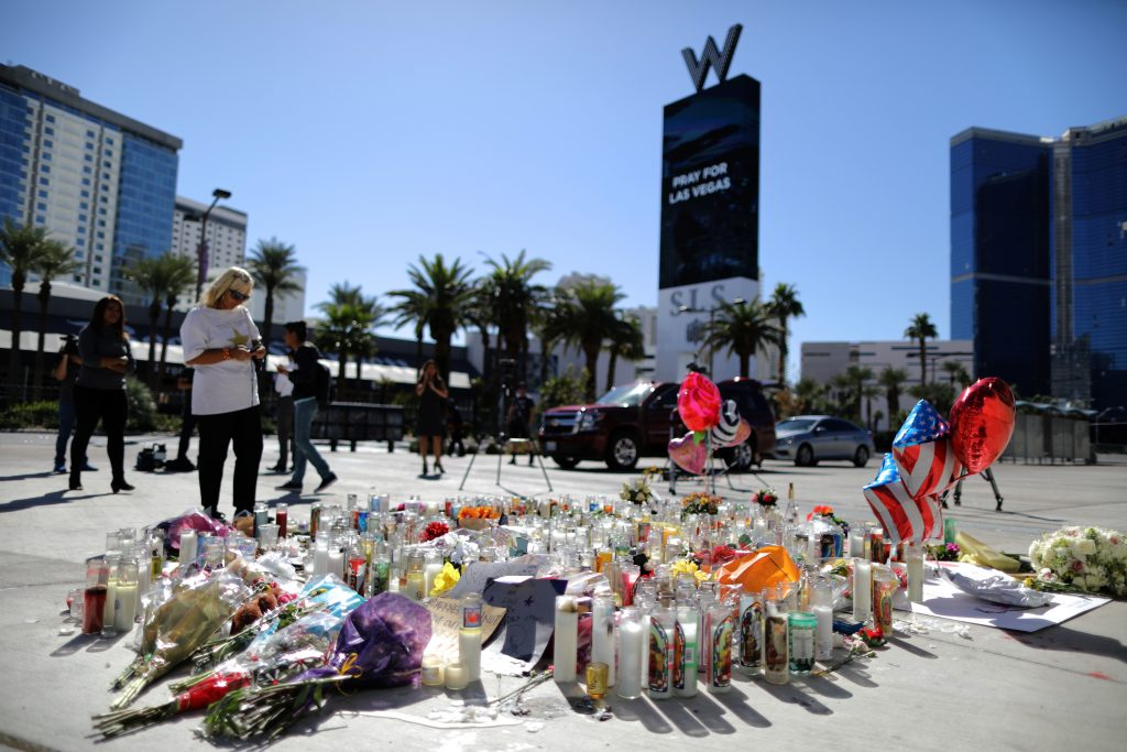 A woman looks at a makeshift memorial on the Las Vegas Strip for victims of the Route 91 music festival mass shooting next to the Mandalay Bay Resort and Casino in Las Vegas, Nevada, U.S. October 3, 2017. REUTERS/Lucy Nicholson - RC1DC22A0F70