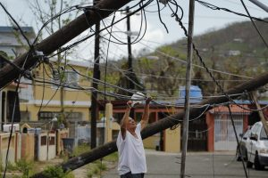 A resident uses a plastic bag to move downed power cables so he can drive underneath them in a neighborhood that has not seen recovery efforts following Hurricane Maria in Ceiba