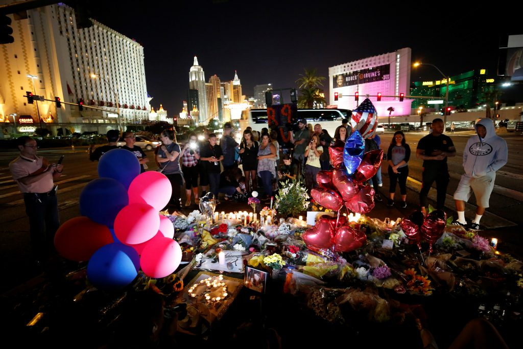 People gather at a makeshift memorial in the middle of Las Vegas Boulevard following the mass shooting. Photo by REUTERS/Chris Wattie