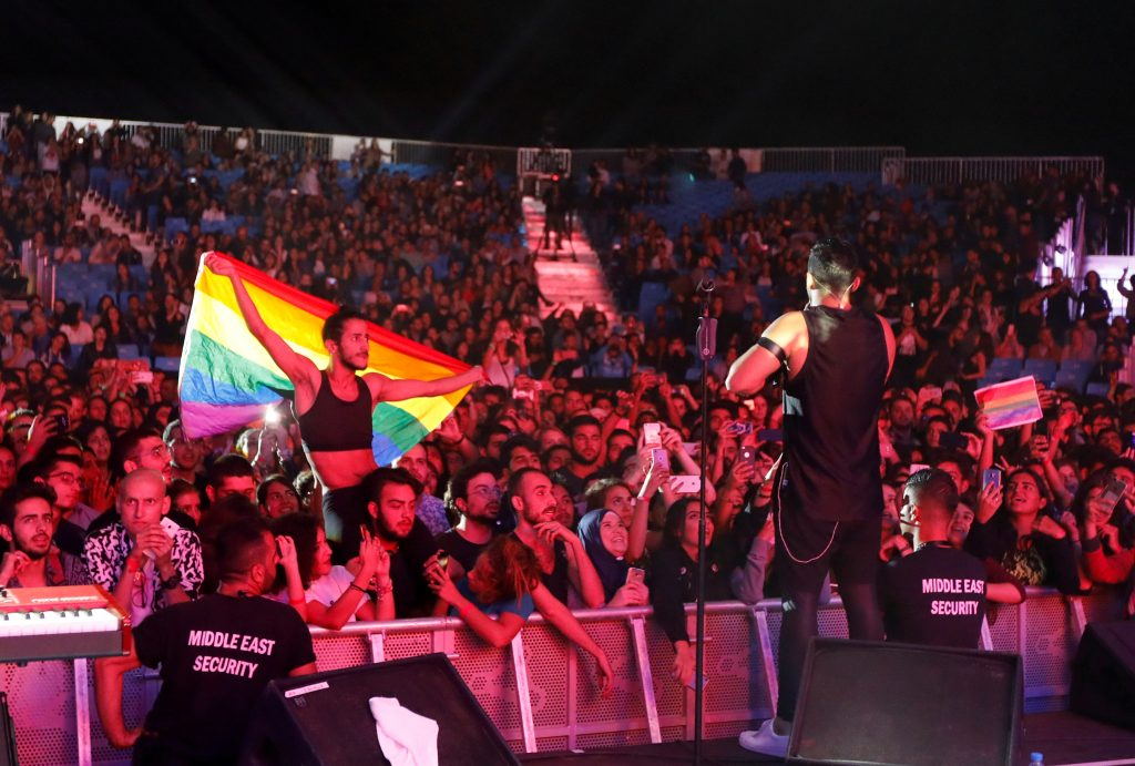 A fan of Lebanese alternative rock band Mashrou' Leila holds a rainbow flag during an Aug. 12 concert at the Ehdeniyat International Festival in Ehden town, Lebanon. Photo by Jamal Saidi/Reuters