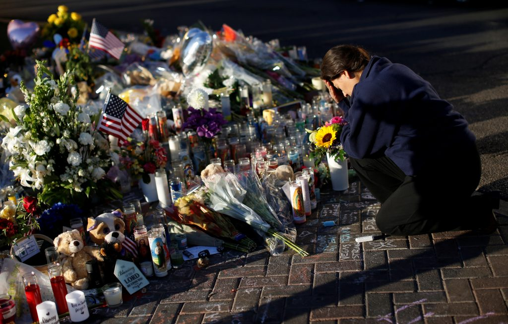 A woman pauses at a makeshift memorial in the middle of Las Vegas Boulevard following the mass shooting in Las Vegas last October. Photo by Reuters.