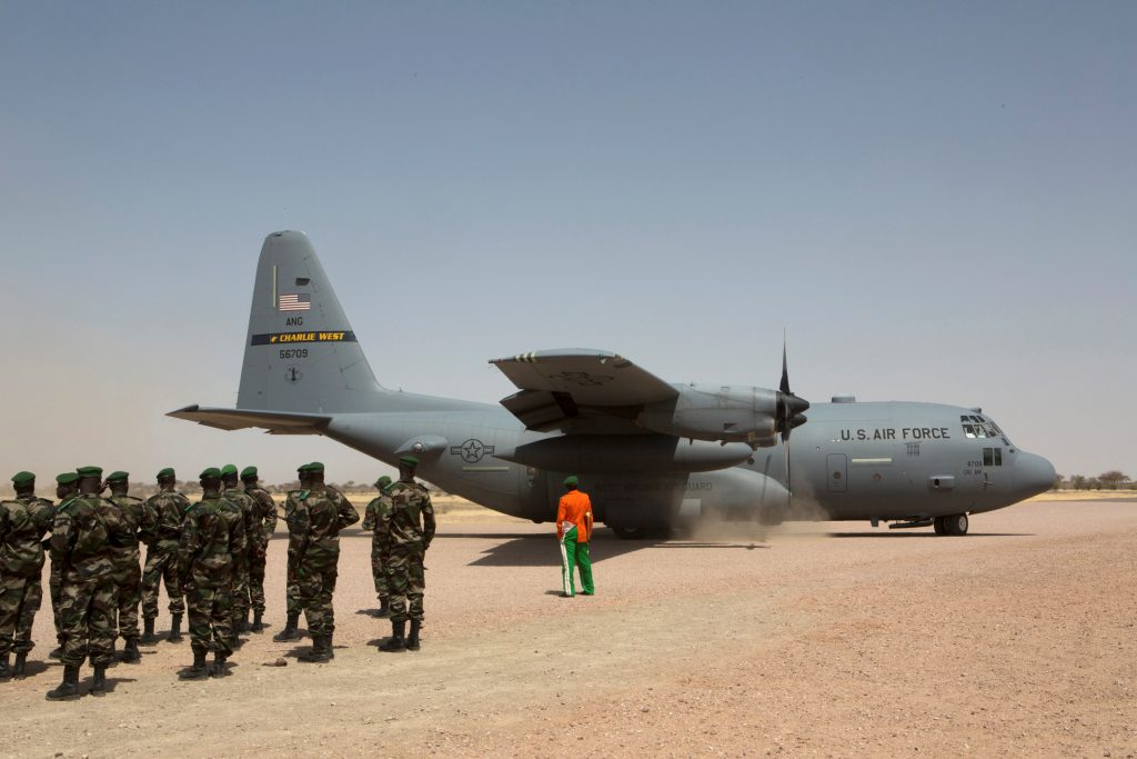 A C-130 U.S. Air Force plane lands as Nigerien soldiers stand in formation during the Flintlock military exercise in Diffa, Niger March 8, 2014. REUTERS/Joe Penney/File Photo