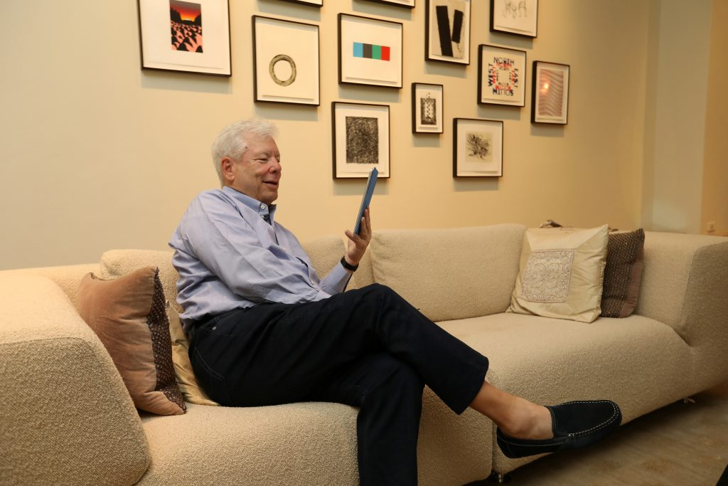"""University of Chicago Booth School of Business economist Richard Thaler talks to his """"Nudge"""" co-author Cass Sunstein via Skype from his living room after winning the 2017 Nobel economics prize, at his apartment in Chicago, Illinois. Photo by Anne Ryan/University of Chicago via Reuters"""