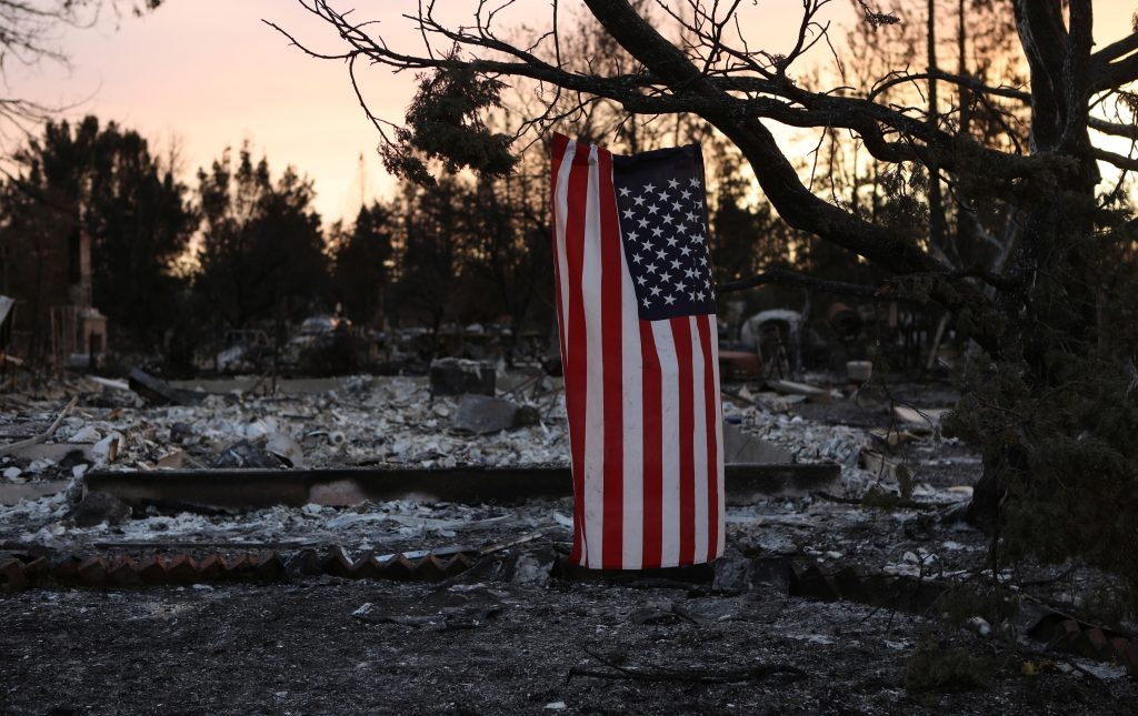 An American flag hangs from a tree in a neighborhood destroyed by wildfire in Santa Rosa, California, U.S., October 12, 2017. REUTERS/Jim Urquhart
