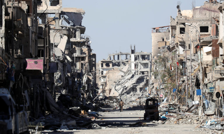 A Syrian Democratic Forces fighter stands amid the ruins of Raqqa, Syria on Oct. 18, 2017. Photo By Erik De Castro/Reuters