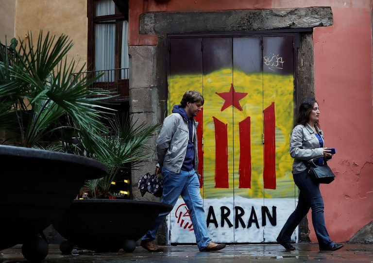 People walk past a doorway painted in the colors of the Catalan separatist flag in Barcelona, Spain, on Oct. 19. Photo by Gonzalo Fuentes/Reuters