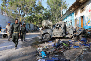 Somali security officers assess the scene of a suicide car bomb explosion, at the gate of Naso Hablod Two Hotel in Hamarweyne district of Mogadishu