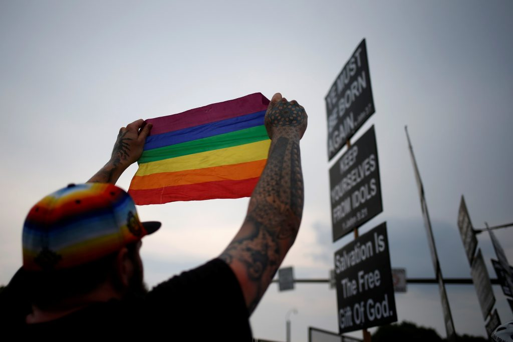 A man holds up the LGBT pride flag towards members of the Westboro Baptist Church near the site of the 2016 Democratic National Convention in Philadelphia, Pennsylvania July 25, 2016. Photo by REUTERS/Adrees Latif