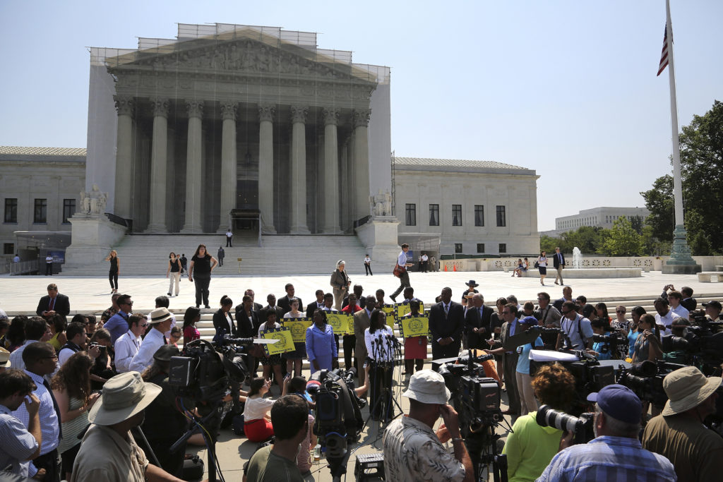 Representatives of the NAACP and other civil rights organizations speak to reporters after the U.S. Supreme Court struck down part of a federal law designed to protect minority voters, at the court's building in Washington