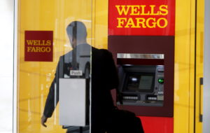 A man walks by an ATM at the Wells Fargo & Co. bank in downtown Denver. Photo by Rick Wilking/Reuters