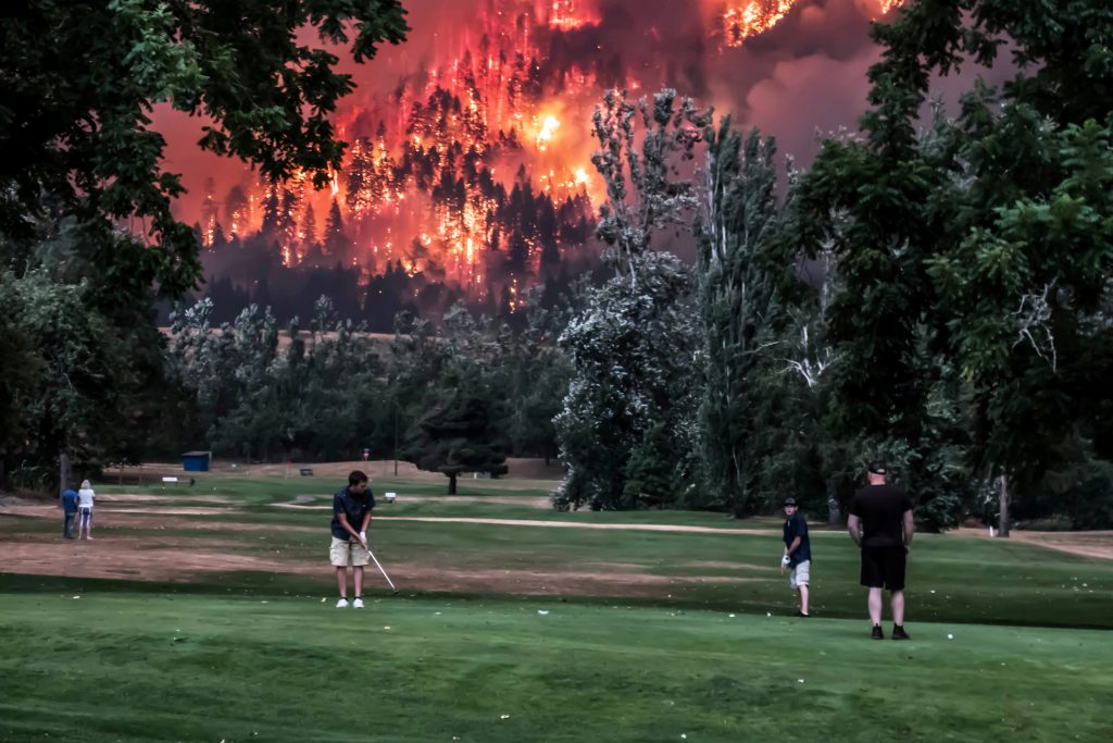 Eagle Creek wildfire burns as golfers play at the Beacon Rock Golf Course in North Bonneville, Washington, U.S. on September 4, 2017. Picture taken on September 4, 2017.  REUTERS/Kristi McCluer