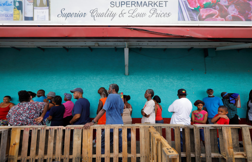 Residents wait behind a makeshift barricade for admission to supermarket in Charlotte Amalie