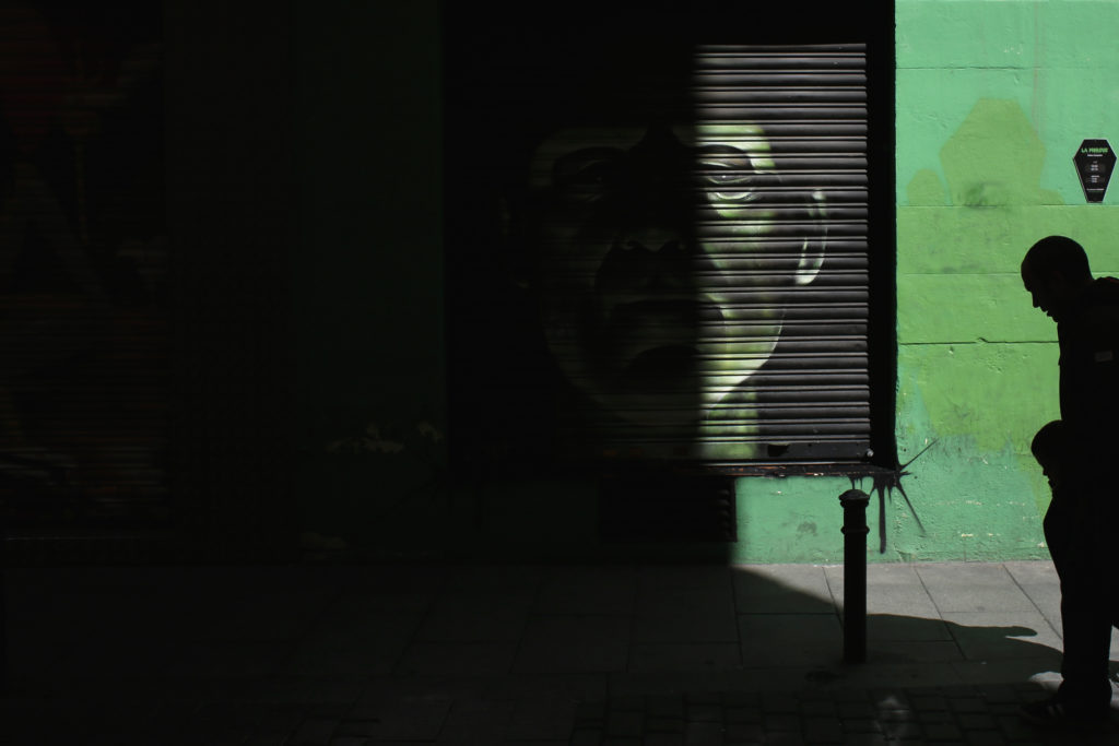 A man and a child walk past a Frankenstein graffiti painted on the roller shutter of a shop at the neighbourhood of La Latina in central Madrid