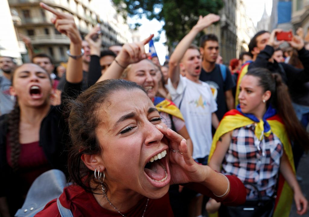 A woman shouts slogans against Spanish National Police during a gathering outside National Police station, in Barcelona, Spain October 2, 2017. REUTERS/Yves Herman - RC1692549590