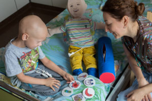 "Alina Khain, a clinical psychologist, shows a patient at Dmitry Rogachev cancer hospital in Moscow the MediKin doll. Photo courtesy of Podari Zhizn (""Gift of Life"" in Russian)"