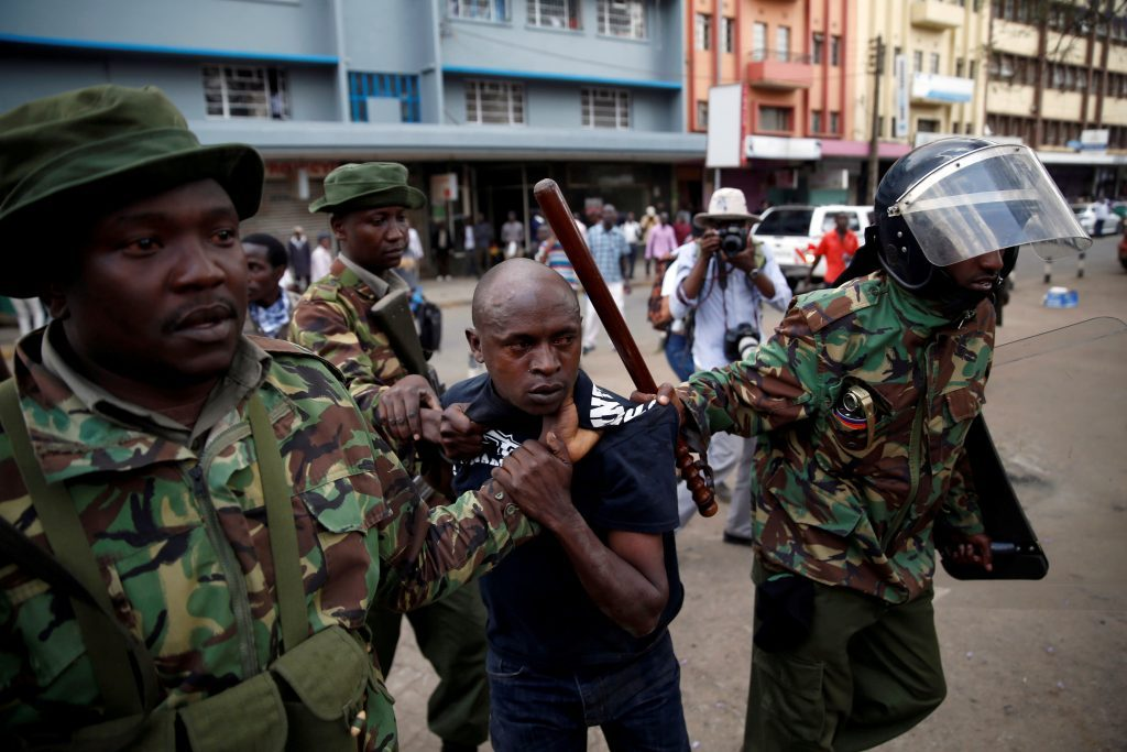 Riot policemen detain a man during clashes between supporters of Kenya's President Uhuru Kenyatta and those of Kenyan opposition National Super Alliance coalition, during a protest in Nairobi, Kenya, on Oct. 11. Photo by Baz Ratner/Reuters