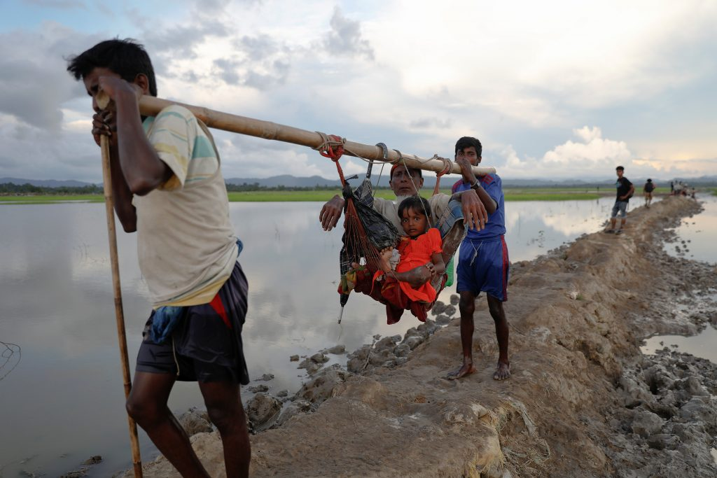 An elderly man and a child are carried as Rohingya refugees who fled from Myanmar make their way through the rice field after crossing the border in Palang Khali, Bangladesh October 9, 2017. REUTERS/Damir Sagolj - RC1E02A14090
