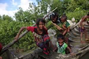 Rohingya Muslims, fled from ongoing military operations in Myanmars Rakhine state make their way through muddy water after crossing the Bangladesh-Myanmar border to reach in Teknaff, Bangladesh on October 08, 2017. Bangladesh said it would be one of the world's biggest refugee cam to house all the 800,000 plus Rohingya muslims who have sought asylum from violence in Myanmar. (Photo by Zakir Hossain Chowdhury/NurPhoto via Getty Images)
