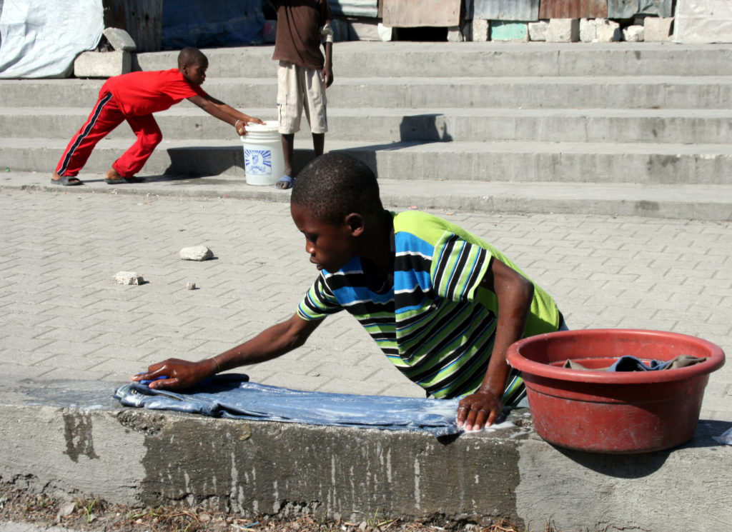 Boys wash their clothes in the streets of Port-au-Prince, Haiti. Photo by Larisa Epatko