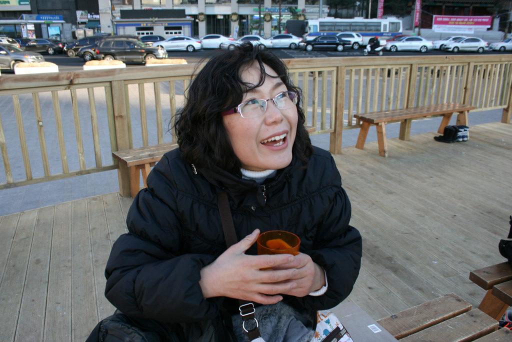 Bangok Ju warms up with a cup of hot chocolate at an ice rink in Seoul, South Korea. Photo by Larisa Epatko/PBS NewsHour