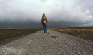 Rear View Of Woman On Road Against Dark cloudy Sky
