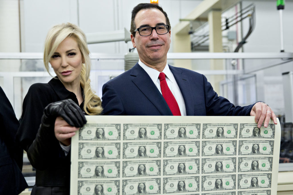 Treasury Secretary Steven Mnuchin and his wife Louise Linton hold a sheet of new $1 bills bearing Mnuchin's name at the U.S. Bureau of Engraving and Printing in Washington, D.C., on Nov. 15. Photo by Andrew Harrer/Bloomberg via Getty Images