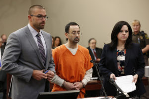 Former Michigan State University and USA Gymnastics doctor Larry Nassar (C) addresses the court with his defense attorneys Matt Newberg (L) and Shannon Smith (R) in Ingham County Circuit Court on November 22, 2017 in Lansing, Michigan. Former USA Gymnastics team doctor Lawrence (Larry) Nassar, accused of molesting dozens of female athletes over several decades, on Wednesday pleaded guilty to multiple counts of criminal sexual conduct. Nassar -- who was involved with USA Gymnastics for nearly three decades and worked with the country's gymnasts at four separate Olympic Games -- could face at least 25 years in prison on the charges brought in Michigan. / AFP PHOTO / JEFF KOWALSKY (Photo credit should read JEFF KOWALSKY/AFP/Getty Images)