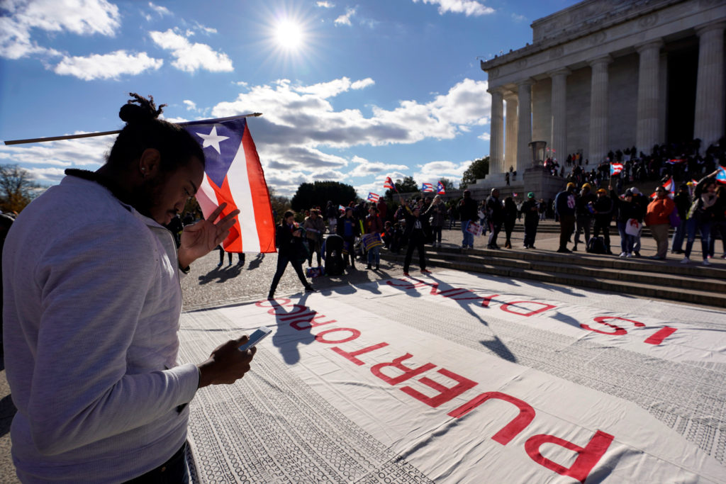 A man participates in the Unity March to highlight the ongoing humanitarian and natural disaster crisis in Puerto Rico, at the Lincoln Memorial in Washington, U.S., November 19, 2017. REUTERS/Yuri Gripas - RC1E578B15E0