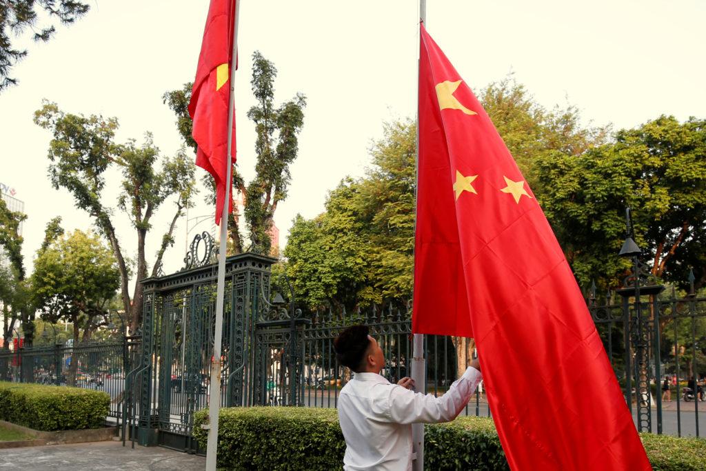 A man raises a Chinese flag next to a Vietnamese flag in Hanoi, Vietnam, on Nov. 2. Photo by Kham/Reuters