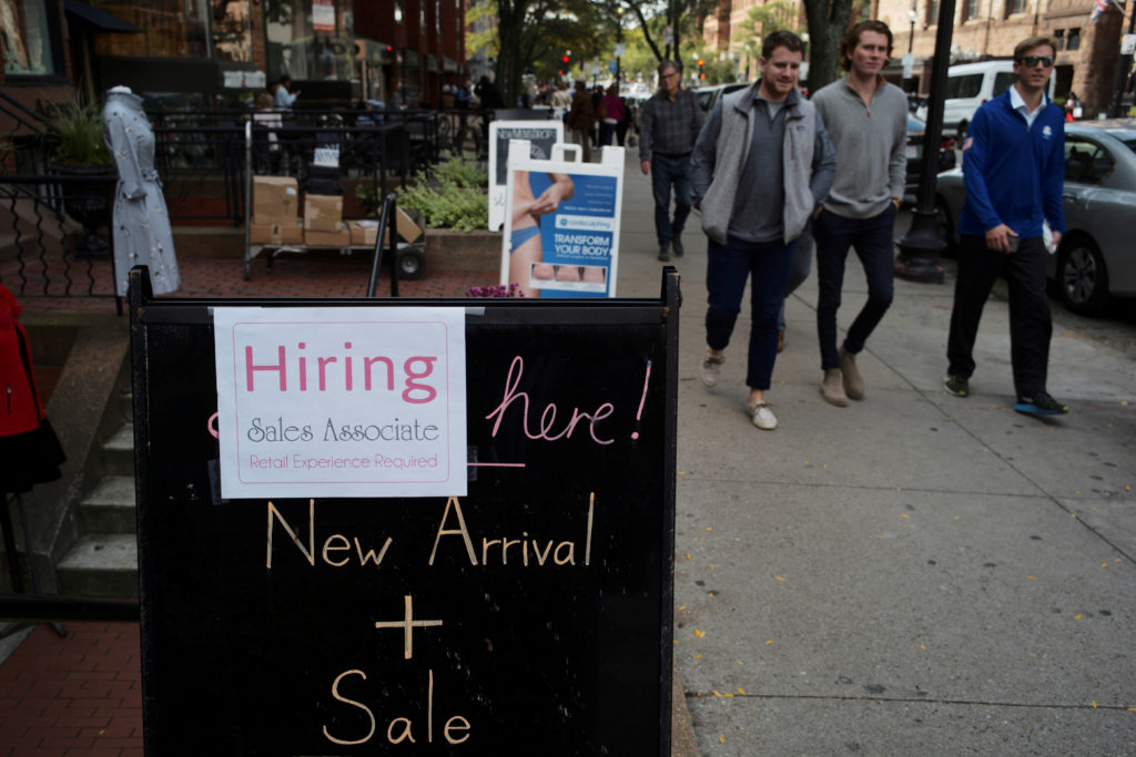 FILE PHOTO: Pedestrians pass a sign advertising a sale and a job opening at a shop on Newbury Street in Boston, Massachusetts, U.S., October 11, 2017. REUTERS/Brian Snyder/File Photo - RC185D6B8230