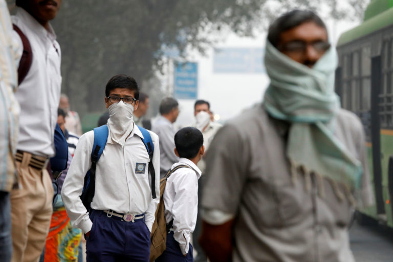 A schoolboy covers his face with a handkerchief as he waits for a bus on a smoggy morning in New Delhi, India, on Nov. 8. Photo by Saumya Khandelwal/Reuters