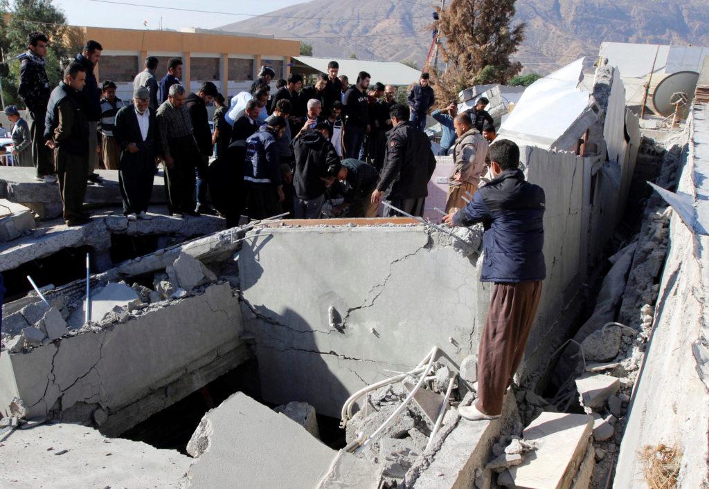 People survey the damage in Darbandikhan, Iraq, on Nov. 13. Photo by Ako Rasheed/Reuters