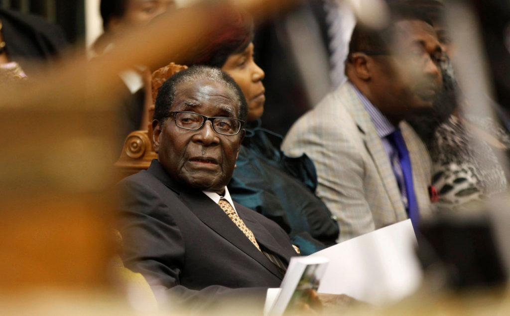 FILE PHOTO: File photo of Zimbabwe's President Mugabe listening as FM Chinamasa presents the country's 2014 National Budget to Parliament in Harare