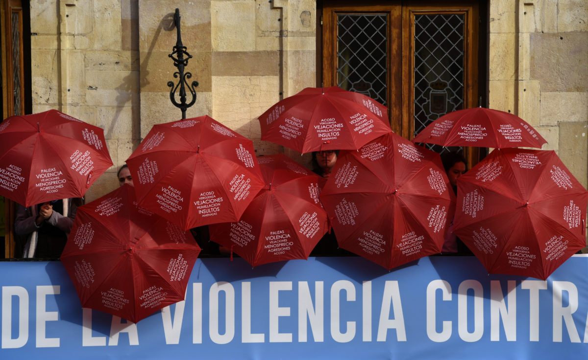 People are covered with red umbrellas to commemorate the victims of gender violence during the UN International Day for the Elimination of Violence against Women in Oviedo