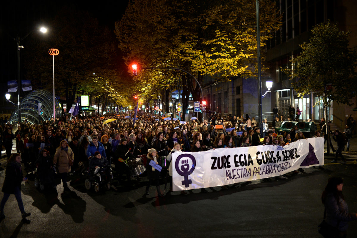 "Protesters carry torches and walk behind a banner reading ""Your truth is Ours. Our Word Counts"" during a demonstration on the World Day for the Elimination of Violence against Women in Bilbao"
