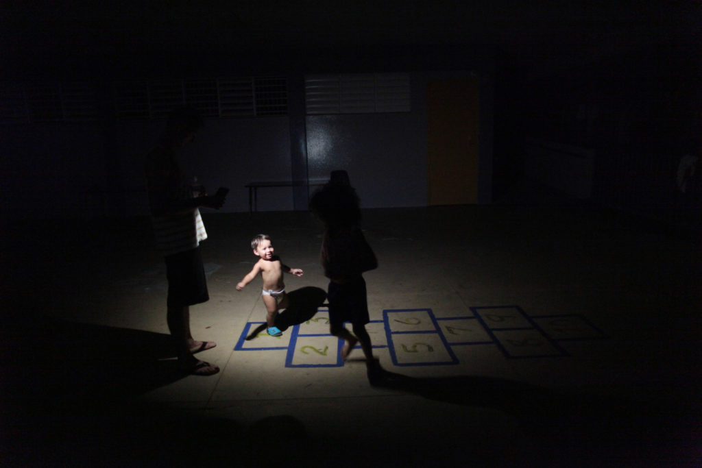 Children play in the light of a flashlight at a school turned shelter, after their home was destroyed when Hurricane Maria hit the island in September, in Toa Baja, Puerto Rico October 18, 2017. Picture taken October 18, 2017. REUTERS/Alvin Baez