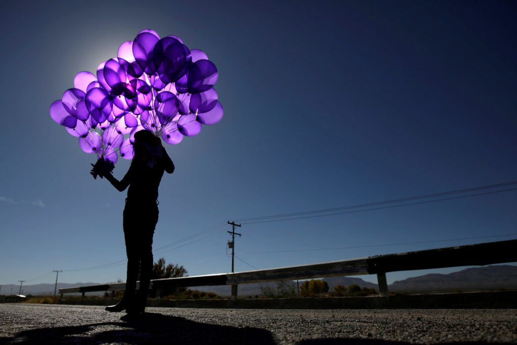 Activist holds purple balloons at El Navajo creek during a ceremony to mark the International Day for the Elimination of Violence Against Women in Praxedis G. Guerrero