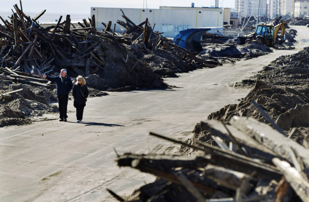 A couple walks through destroyed sections of boardwalk ripped apart by superstorm Sandy along Shore Front Parkway in the Rockaways area of the Queens borough of New York, November 4, 2012. Victims of superstorm Sandy on the U.S. East Coast struggled against the cold early on Sunday amid fuel shortages and power outages even as officials fretted about getting voters displaced by the storm to polling stations for Tuesday's presidential election. Photo by Lucas Jackson/REUTERS