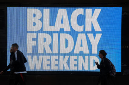 Shoppers are seen walking past an electronic billboard advertising the retail so-called 'Black Friday' date and event in London, Britain, November 23, 2017. Photo by Toby Melville/REUTERS